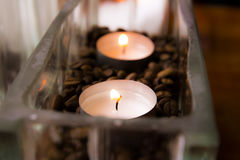 Peaceful candles giving out warm light. 2 warm peaceful candles setting a good mood in a glass vase. Taken on the island of Bornholm royalty free stock image