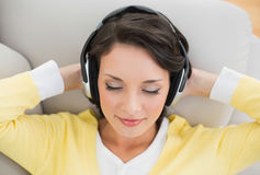 Peaceful casual brunette in yellow cardigan enjoying music Stock Photo