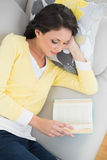 Peaceful casual brunette in yellow cardigan reading a book Stock Image
