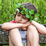 Peaceful child with foliage crown closing her eyes to sleep Royalty Free Stock Image