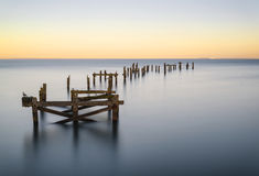 Peaceful concept landscape image of smooth sea and pier ruins Royalty Free Stock Photo