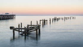 Peaceful concept landscape image of smooth sea and pier ruins Stock Images