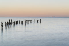 Peaceful concept landscape image of smooth sea and pier ruins Royalty Free Stock Images