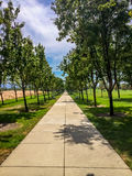 A peaceful concrete walkway in the park. Royalty Free Stock Images