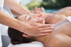 Peaceful couple enjoying couples massage poolside Royalty Free Stock Images