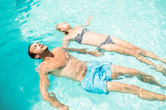 Peaceful couple floating in the pool Royalty Free Stock Images