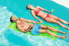 Peaceful couple on lilos holding cocktails. In the pool Stock Photography
