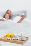 Peaceful couple sleeping with breakfast tray on bed Stock Photography