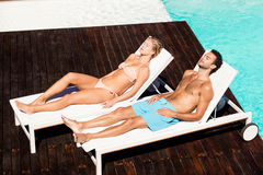 Peaceful couple sunbathing on deck chairs Stock Images
