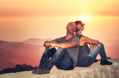 Peaceful couple in vacation. Happy peaceful couple sitting back to back to each other and enjoying amazing view on a majestic mountaing in mild sunset light royalty free stock photography