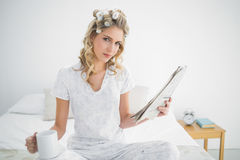 Peaceful cute blonde wearing hair curlers holding newspaper Stock Photos