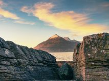 Peaceful dawn at Elgol bay. Low angle  overlooking of offshore rocks and smooth sea, mountains Stock Image