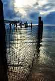 Peaceful day ends sun setting over fishing nets wharf & sea royalty free stock image