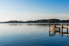 A peaceful day at a Missouri Lake. A midwestern lake in Missouri. It is so peaceful and shows lake with trees, sky, and a pier with the water rifting in small Stock Photo