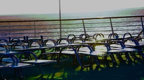 Peaceful day at sea. Lounge chairs stacked against the railing on a beautiful day at sea Royalty Free Stock Photos
