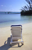 Peaceful Deck Chair. A lounge chair waits for someone to relax in front of the waters of the Bahamas royalty free stock image