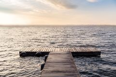 Peaceful empty wooden bridge in the morning sun. Peaceful scene with empty wooden bridge in the morning sun. Endless lake with small waves with reflecting royalty free stock images