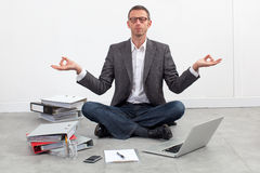 Peaceful entrepreneur practicing yoga on the office floor. Zen business concept - peaceful entrepreneur practicing yoga on the floor of the office, sitting Royalty Free Stock Photography