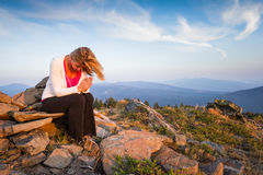 Peaceful environment. Beautiful woman praying on the top of a mountain Royalty Free Stock Images