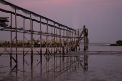 Peaceful evening on the shore, with scenic pink sunset reflected on water ant metallic pier; adriatic sea. Peaceful evening on the shore in Italy royalty free stock photos