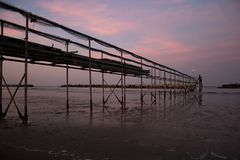 Peaceful evening on the shore, with scenic pink sunset reflected on water ant metallic pier; adriatic sea. Peaceful evening on the shore in Italy royalty free stock image