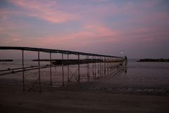 Peaceful evening on the shore, with scenic pink sunset reflected on water ant metallic pier; adriatic sea. Scenic pink sunset reflected on water and metallic stock images