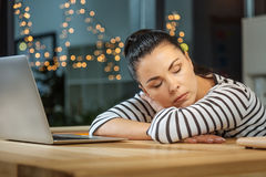 Peaceful exhausted woman falling asleep. Too tired. Peaceful exhausted hard working woman sitting at the desk and falling asleep while being at work Stock Image