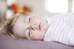 Peaceful face of baby sleeping. Face of blonde caucasian baby nineteen month age with pink and white stripped jersey sleeping on brown sheets king bed royalty free stock photos