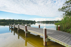 Peaceful Fishing Pier on Bayou. Fishing pier and boat launch in Bayview Park on Bayou Texar in Pensacola, Florida in early morning light Royalty Free Stock Photography