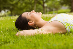 Peaceful fit brunette lying on the grass Royalty Free Stock Photos