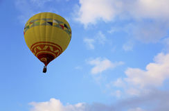 Peaceful Flight 2. A hot air balloon passes in slightly cloudy- blue skies stock photography