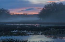 Foggy sunrise at the lake. Peaceful foggy sunrise on the lake. The sunrise colors the sky in brilliant vivid colors Royalty Free Stock Photos