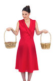 Peaceful glamorous model in red dress holding baskets Stock Photo