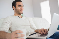 Peaceful handsome man having coffee while using his laptop Stock Images