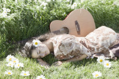 Peaceful happy hippie. Hippie woman lying in the grass and sun with guitar and daisies royalty free stock images