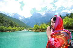 Peaceful happy life, Asian Chinese prey before snow capped mountain. Asian Chinese woman yoga by a lake, Yulong snow capped mountains on the background Royalty Free Stock Photos