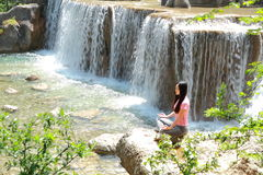 Peaceful happy life, careless Asian Chinese woman do yoga before waterfall. Asian Chinese woman yoga by a lake, Yulong snow capped mountains on the background Royalty Free Stock Photo
