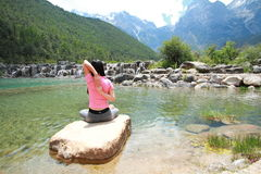 Peaceful happy life, careless Asian Chinese woman yoga. Asian Chinese woman yoga by a lake, Yulong snow capped mountains on the background, beautiful landscape Royalty Free Stock Images