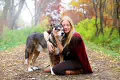Peaceful Happy Woman Hugging German Shepherd Dog While Walking i. A happy, peaceful young woman has stopped walking her dog along a path in the autumn forest to Royalty Free Stock Photos