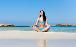 Woman meditating on the beach Stock Image