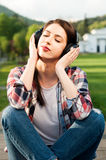 Peaceful hipster female enjoying music outside in the park Stock Images