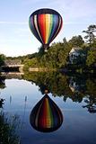 Peaceful Hot Air Balloon over river in Vermont. Quechee Hot Air Balloon Festival hot air balloon floats over river reflecting its rainbow colors near the Quechee Stock Photos