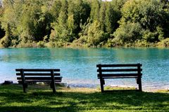Free Peaceful Image Of Deep Blue Green Water Of Lake With Two Benches For Sitting To Enjoy The Scenery Stock Image - 138472441