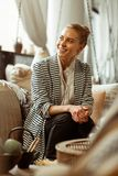 Cheerful good-looking blonde lady sitting on comfortable couch. Peaceful lady . Cheerful good-looking blonde lady sitting on comfortable couch in striped jacket stock photos