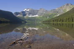 Peaceful Lake. A piece of driftwood pointing towards a mountain range from a peaceful lake Stock Image