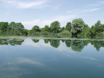Peaceful lake with clouds reflected in water stock images