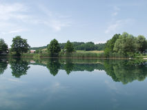 Peaceful lake with clouds and trees reflected in water stock photo
