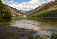 Peaceful lake Glendalough wicklow mountains, ireland. The sun is lighting up certain parts of the landscape royalty free stock images