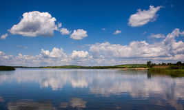 Peaceful lake landscape in village on background of blue sky Stock Photography