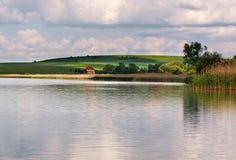 Peaceful lake landscape in the village under blue sky Stock Images